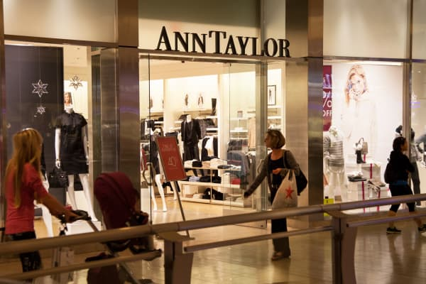 Shoppers pass in front of an Ann Taylor store