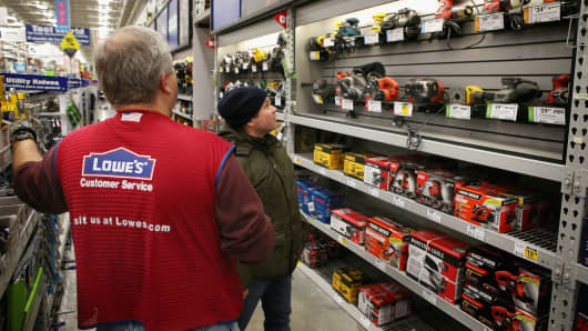 An employee helps a customer shop for a sander at a Lowe's home improvement store in Chicago.