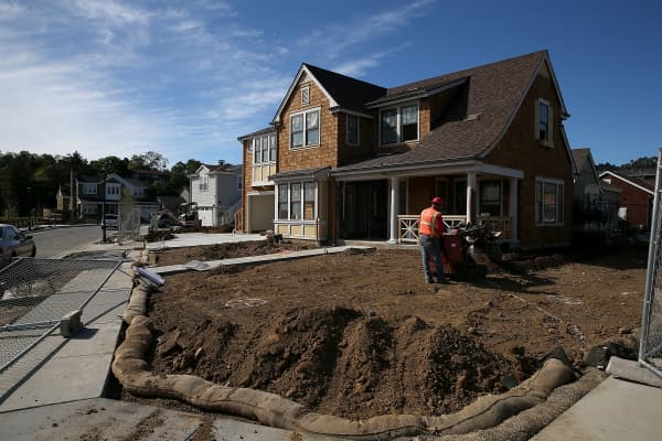 A worker digs a trench in front of a home under construction at a new housing development in Larkspur, California.