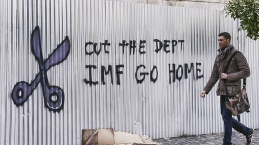 A citizen passes by graffiti against the IMF on February 10, 2015 in Athens, Greece.