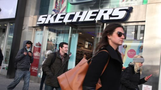 Pedestrians pass in front of a Skechers store in New York.