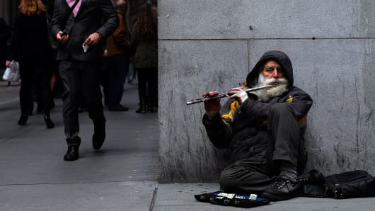 A musician plays a flute sitting on the footpath next to New York Stock Exchange (NYSE) building in New York.
