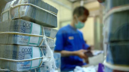 An employee of BNI bank, an Indonesian state-owned bank, prepares rupiah banknotes for their ATMs and branch offices.