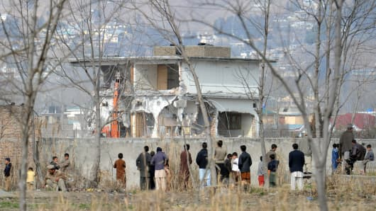 Local residents watch the demolition of the compound where Osama bin Laden was killed in Abbottabad on February 26, 2012