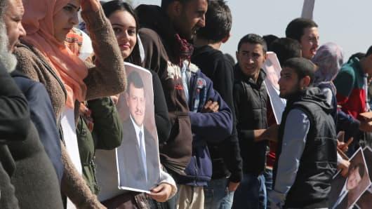 Jordanians stand along the way between Amman and Queen Alia airport in Jordan waiting to greet Jordan's King Abdullah II.
