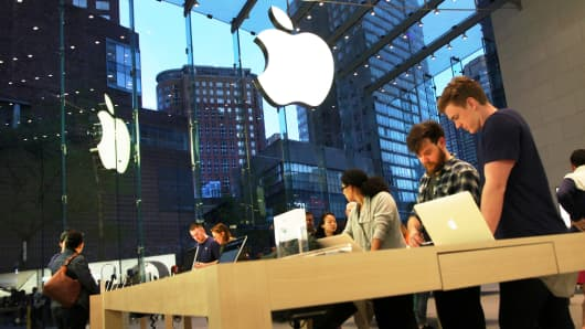 Shoppers and salespeople at an Apple store in New York.