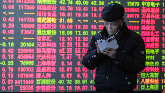 Investors watch a digital screen displaying the prices of China's stock market in Hangzhou, Zhejiang province of China.