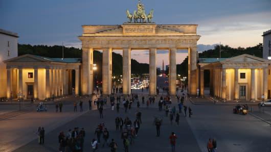 People walk on Pariser Platz square in front of the illuminated Brandenburg Gate in Berlin.