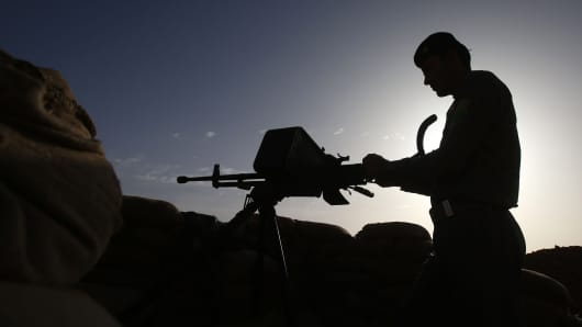 An Iraqi fighter from the Shiite Muslim Al-Abbas popular mobilization unit monitors from his position near the village of Nukhayb west of Baghdad, on May 19, 2015.