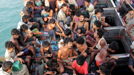 Rohingya migrants sit in their boat as they are towed closer to land by Acehnese fishermen, off the coast near the city of Geulumpang in Indonesia's East Aceh district of Aceh province, before being rescued on May 20, 2015.