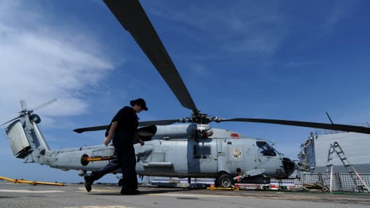 A US navy  officer walks past a SeaHawk on board the guided missile destroyer USS Howard docked near the disputed Spratly islands,
