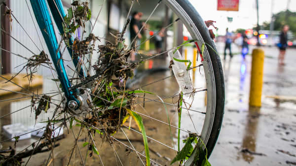 Debris from flooding waters are stuck in the spokes of a bicycle wheel in Austin, Texas.