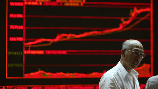 An investor and the electronic board at a stock exchange hall on May 25, 2015, in Beijing.