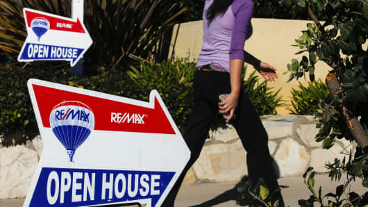 A woman walks past RE/MAX Holdings signage while arriving for an open house in Redondo Beach, Calif.