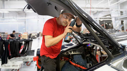 A worker installs interior trim on a Telsa Model S sedan.