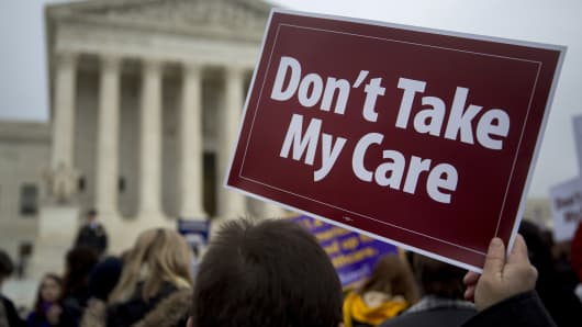 Demonstrator Elodie Huttner holds a sign in support of President Barack Obama's health-care law, Obamacare, in front of the U.S. Supreme Court in Washington, on Wednesday, March 4, 2015.