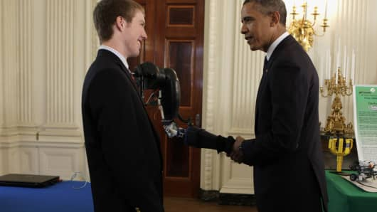 Barack Obama shakes hands with a robotic arm, created by Easton LaChappelle