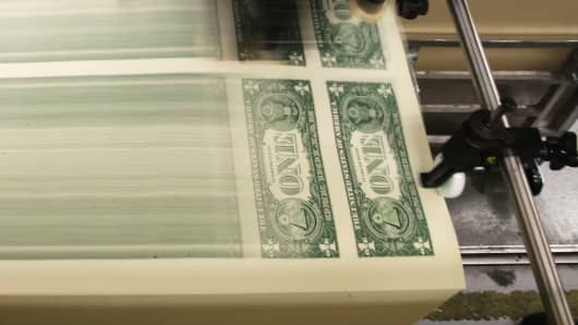 Sheets of one dollar bills run through the printing press at the Bureau of Engraving and Printing in Washington, DC.
