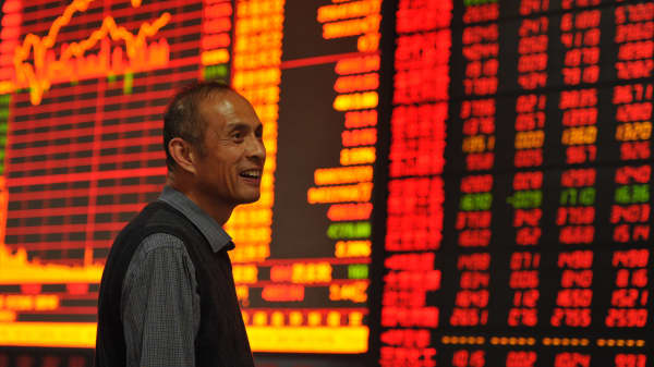 An investor smiles during his observing stock market at an stock exchange in Fuyang, Anhui province of China.