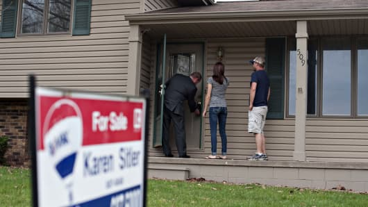 A real estate agent opens the front door to potential home buyers in Washington, Ill.