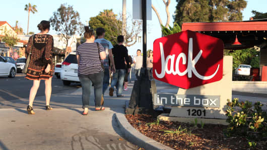 People pass in front of a Jack in the Box restaurant in Laguna Beach, California.