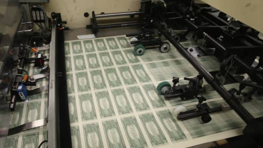 Sheets of one dollar bills run through the printing press at the Bureau of Engraving and Printing on March 24, 2015 in Washington, DC.