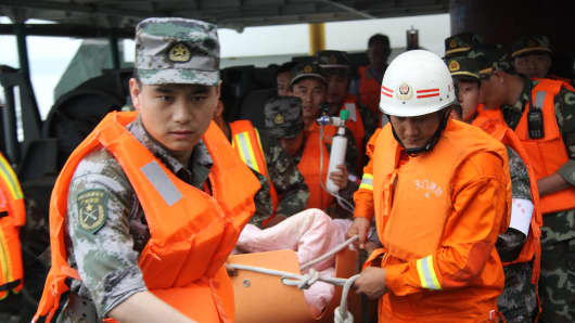 Rescuers carry a survivor from the capsized ship in the Yangtze River, China.