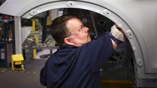 An employee inspects the wheel well of a BMW X4 SUV at the BMW assembly plant in Greer, South Carolina.