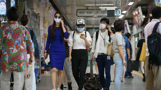 People wearing face masks walk through a subway station in Seoul.