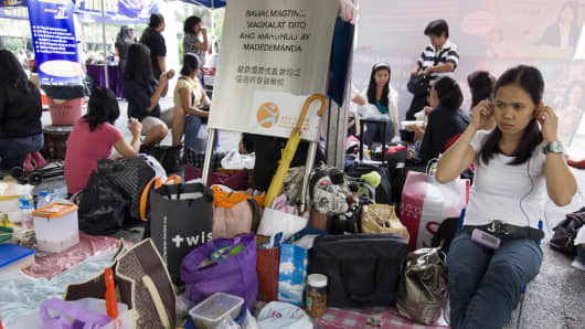 Filipino maids with food, hampers and bags reserve place to sit in Statue Square in central Hong Kong for a Sunday social function