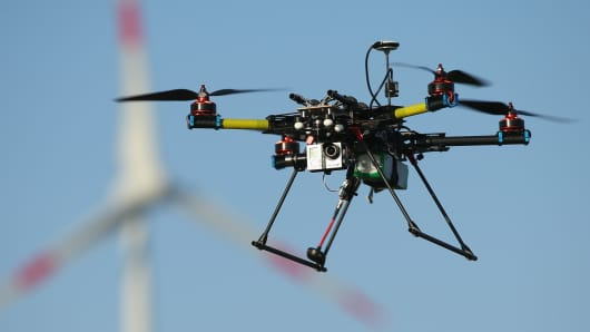 A multirotor quadcopter drone used for aerial photography flies near a wind turbine.