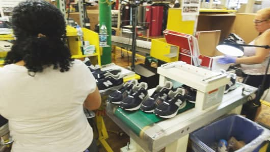 New Balance manufacturing associates at their Lawrence, Massachusetts, factory inspect sneakers before placing them in boxes