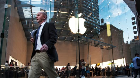 Pedestrians pass in front of an Apple store in New York.