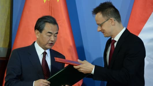 Chinese Foreign Minister Wang Yi and Hungarian Minister of External Economy and Foreign Affairs Peter Szijjarto exchange their co-operation agreement at the Conference Hall of the ministry in Budapest on June 6, 2015