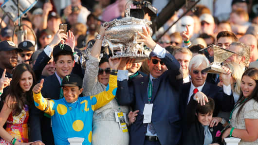 Jockey Victor Espinoza, owner Ahmed Zayat and trainer Bob Baffert (left to right), celebrate with the Belmont Stakes and Triple Crown Trophies after American Pharoah won the 147th running of the Belmont on June 6, 2015, in Elmont, New York.