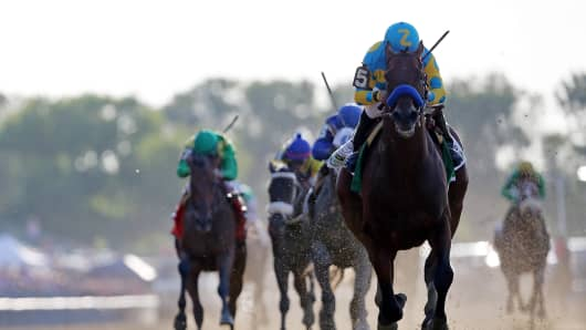 American Pharoah #5, ridden by Victor Espinoza, comes down the final stretch ahead of the field on his way to winning the 147th running of the Belmont Stakes at Belmont Park on June 6, 2015 in Elmont, New York.