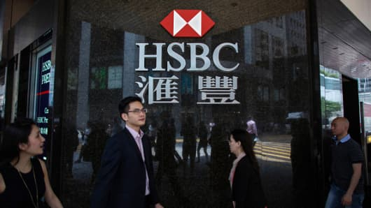 Pedestrians walk past a signage for HSBC Holdings Plc displayed outside a bank branch in the Central district of Hong Kong, China