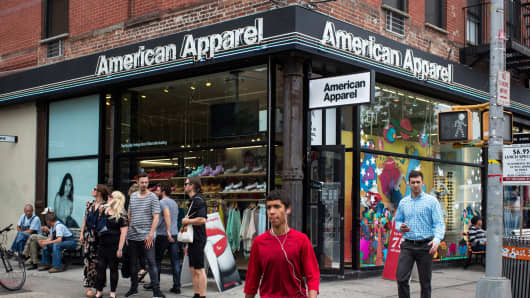 People walk past an American Apparel store in New York City.