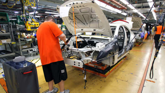 A worker helps assemble a 2013 Cadillac ATS at the General Motors Lansing Grand River Assembly Plant in Lansing, Michigan.