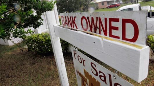 A bank owned sign is seen in front of a foreclosed home.