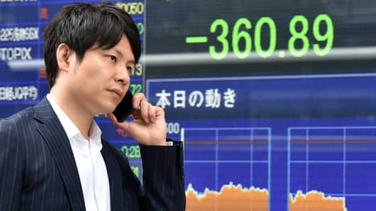 A man walks past a share prices board in Tokyo on June 9, 2015.