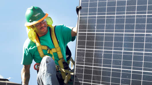 An employee for SolarCity installs solar panels on the roof of a home in Palo Alto, Calif.