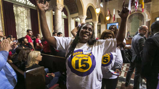 Workers react as the Los Angeles City Council votes 13-1 to raise the minimum wage to $15 an hour by 2020.