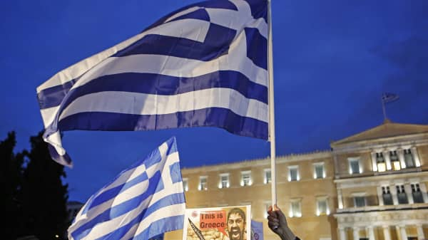 Greek flags fly outside the Greek Parliament during a protest in Athens, Greece.