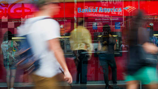Customers use automated teller machines (ATM) as pedestrians pass in front of a Bank of America Corp. branch in New York.