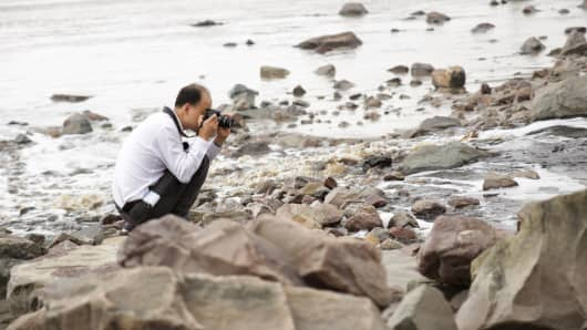Ma Jun, head of the Institute of Public and Environmental Affairs, photographing water outfall pipe, documenting industrial pollution in China.