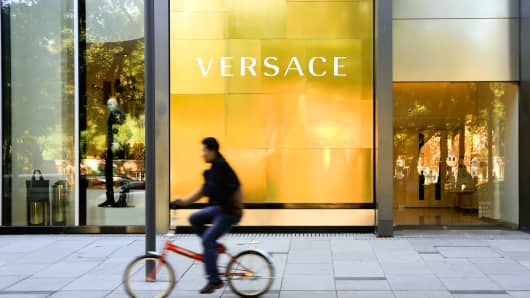 A man rides a bicycle past a Gianni Versace store in Beijing, China.