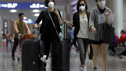 Tourists wear masks as a precaution against the MERS virus at the Incheon International Airport in South Korea.