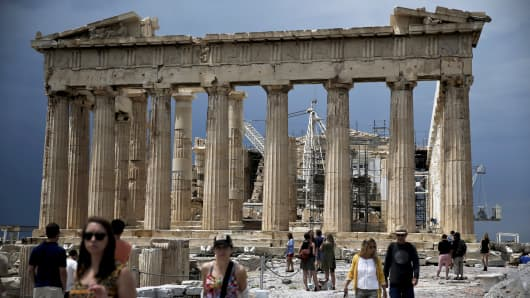 People visit the Acropolis hill with the ancient Parthenon temple seen in the background, Athens, Greece.