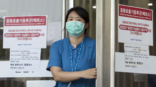 A hospital worker wears a mask as a precaution against the MERS virus at Seoul National University Hospital in Seoul, South Korea, Friday, June 12, 2015.
